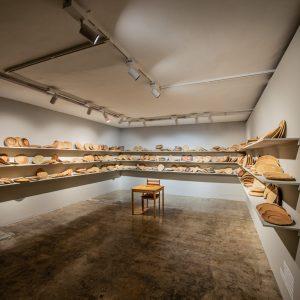 installation view/bread dough, wooden shelves, chair, desk,, sulfur